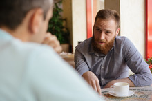 Young Bearded Man Explain And Discuss Something With His Interlocutor Friend Sitting Indoors Cafe With Cup Of Coffee