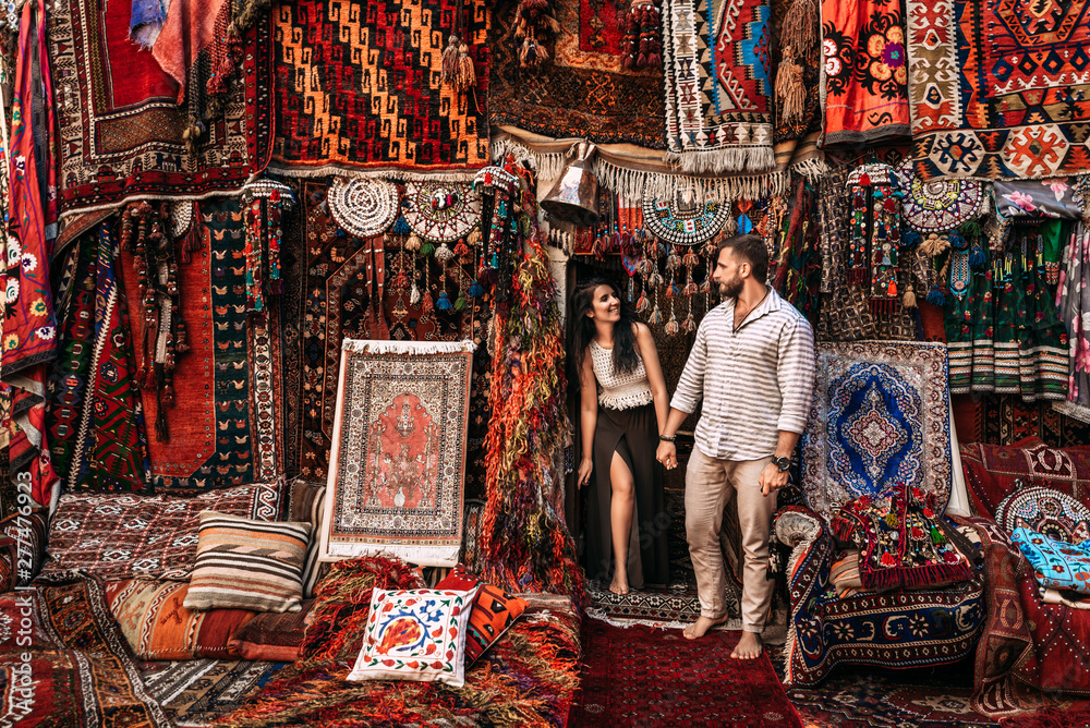 Fototapety, obrazy: Man and woman in the store. Couple in love in Turkey. Man and woman in the Eastern country. Happy couple travels the world. Persian shop. Tourists in store. Oriental carpet. Istanbul. Follow me