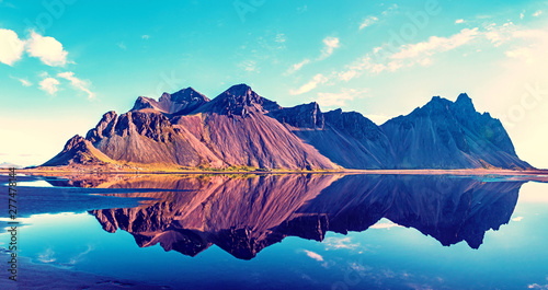 Foto auf Leinwand Blaue Nacht Exciting beautiful landscape with most breathtaking mountains Vestrahorn on the Stokksnes peninsula in the mirror of the lake. Exotic countries. Amazing places. (Meditation, antistress - concept).