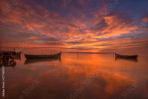 Colorful sunrise at the sea with boats floating on calm water and clouds reflecting on the water