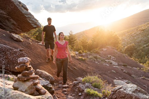 Fototapeta Couple walking down a mountain trail at sunset. obraz na płótnie