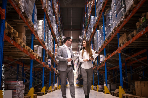 Managers visiting warehouse. Business people walking through large distribution center and talking about increasing production and organization.