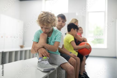 Fototapeta  Sad pupil sitting in front of his classmates.