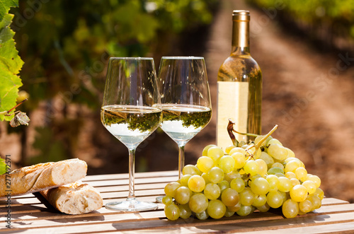 Fototapeta still life with glass of White wine grapes and bread on table in field obraz
