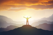 Climber Arms Up Outstretched On Mountain Top Looking At Inspirational Landscape.