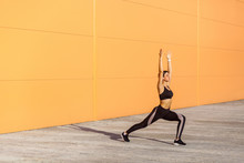 Side View Of Young Attractive Woman Wearing Black Sporwear Practicing Sport Exercises In Morning On Street, Standing In Warrior One Exercise, Virabhadrasana Pose, Orange Wall Background, Outdoor