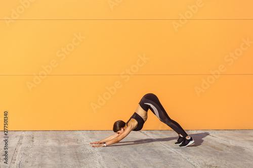 Slika na platnu Young sporty woman practicing yoga, doing downward facing dog exercise, adho muk