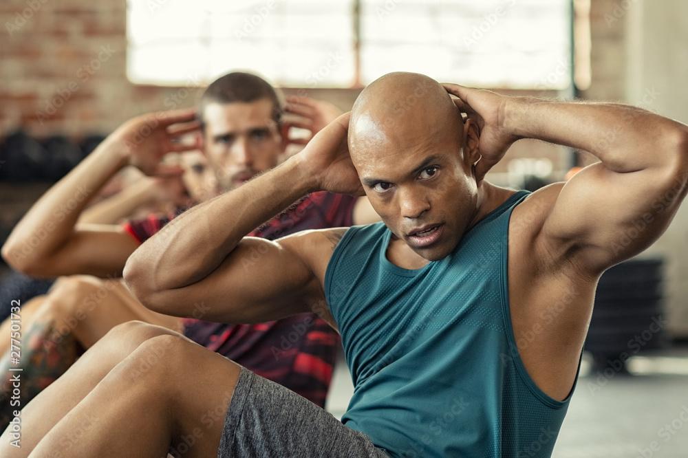 Fototapeta Men doing sit ups workout