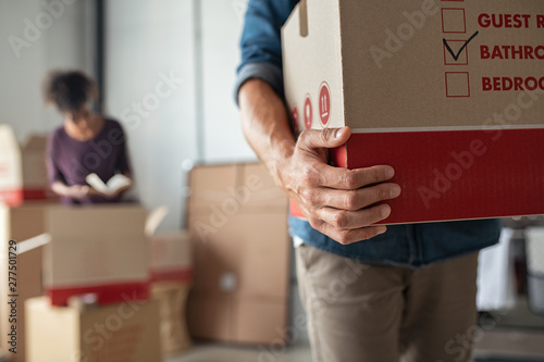 Hands holding cardboard box during relocation Fototapeta