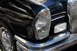 Detail of luxury vintage black car, light, bumper and wheel