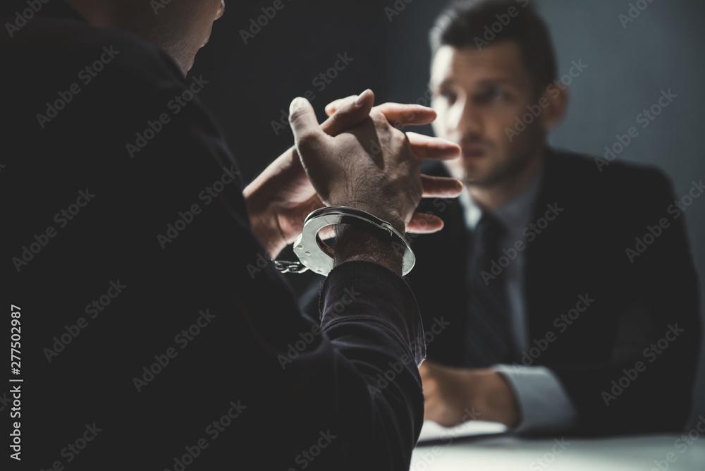 Fototapeta Criminal man with handcuffs being interviewed in interrogation room