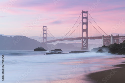 Classic panoramic view of famous Golden Gate Bridge seen from scenic Baker Beach in beautiful golden evening light on sunset with blue sky and clouds in summer, San Francisco, California, USA