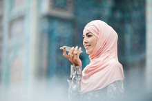 Cheerful Confident Young Middle-eastern Woman In Pink Hijab Standing Against Ornamental Building And Chatting Via Voice Messages On Phone