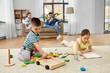 canvas print picture - childhood, leisure and family concept - brother playing toy blocks and sister drawing by crayons at home