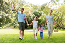 Family, Leisure And People Concept - Happy Mother With Picnic Basket, Father And Two Daughters Walking In Summer Park