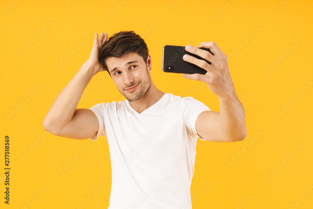 Fototapeta Man in casual white t-shirt take a selfie by mobile phone isolated over yellow background.