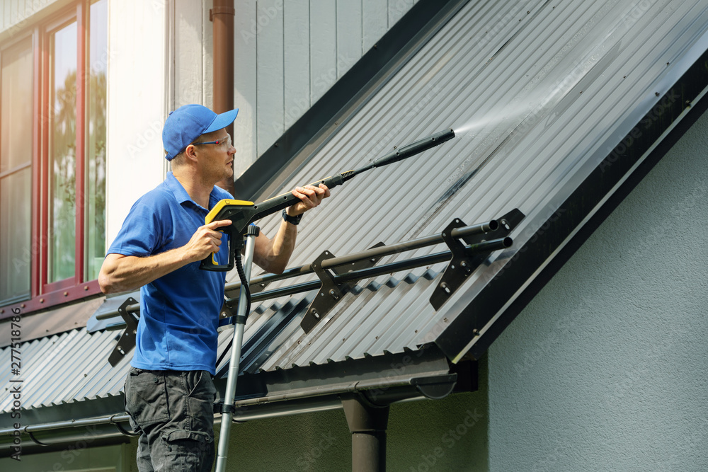 Fototapety, obrazy: man standing on ladder and cleaning house metal roof with high pressure washer