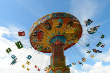 June 10, 2018: Children Ride On The Carousel In An Amusement Park Against A Blue Sky. Cheboksary. Russia.