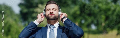 panoramic shot of man listening to music in headphones - 277523373