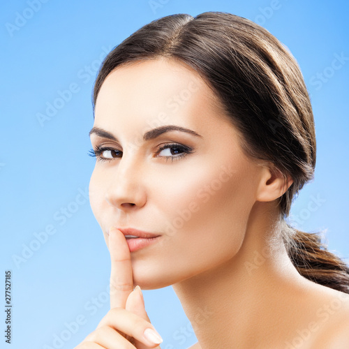 Woman keeping finger on her lips, on blue