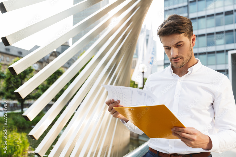 Fototapety, obrazy: Concentrated handsome young business man standing near business center holding clipboard with documents.