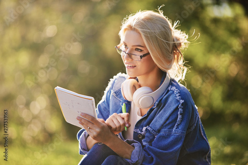 Portrait of a smiling young woman student in eyeglasses sitting in nature park. Listening music with headphones and writing notes. Online and remote education concept - 277539163
