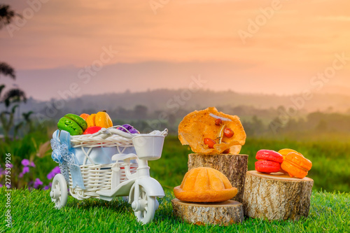 Poster Picnic Malaysia traditional sweet as known as Baulu or Bahulu and Rempeyek with Macaron on wooden sliced during beautiful sunrise.