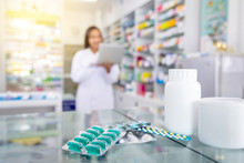 Capsules Medicine And White Medicine Bottles On Table In Drugstore With Blurred Background Of Pharmacist And Pharmacy.