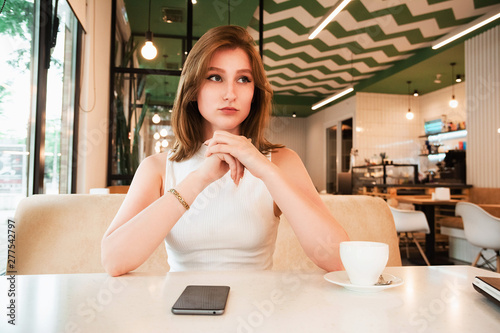 Fotografia  Girl is waiting for a meeting in cafe