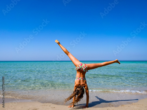 Fotografie, Tablou  Slim and athletic girl doing a cartwheel on a wonderful beach with crystal clear