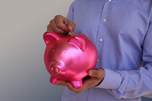 Male Businessman In A Blue Shirt Holding A Pink Piggy Bank In His Hands, Dropping A 2 Euro Metal Coin Into Slot, Concept Banking, Business