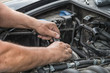 Two hands carry out repairs in the engine compartment of a car..