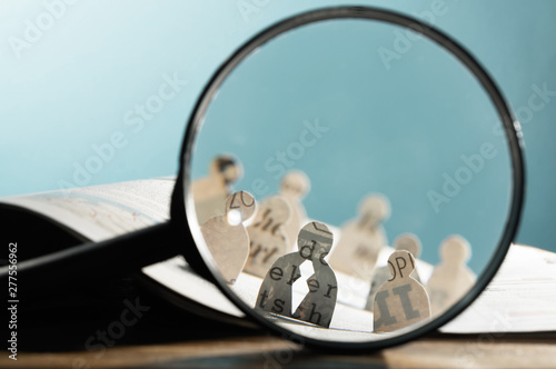 Obraz Business recruitment or hiring photo concept. Looking for talent. Icons of candidates are standing on open newspaper under magnifier. - fototapety do salonu