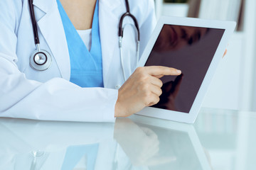 Female doctor using tablet computer while sitting at the workplace, close-up of hands. Medicine, healthcare and help concept