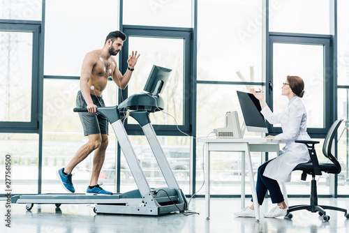 doctor sitting at computer desk and conducting endurance test with sportsman in gym