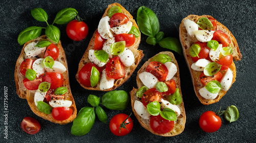 Foto  Bruschetta with tomatoes, mozzarella cheese and basil on a cutting board