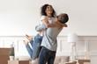 Leinwanddruck Bild - African husband lifting happy wife celebrating moving day with boxes