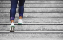 Female Runner Athlete Doing A Stairs Climbing. Running Woman Doing Run Up Steps On Staircase In Urban City. Doing Cardio Sport Workout. Exercise Outside In Summer. Activewear Leggings And Shoes.