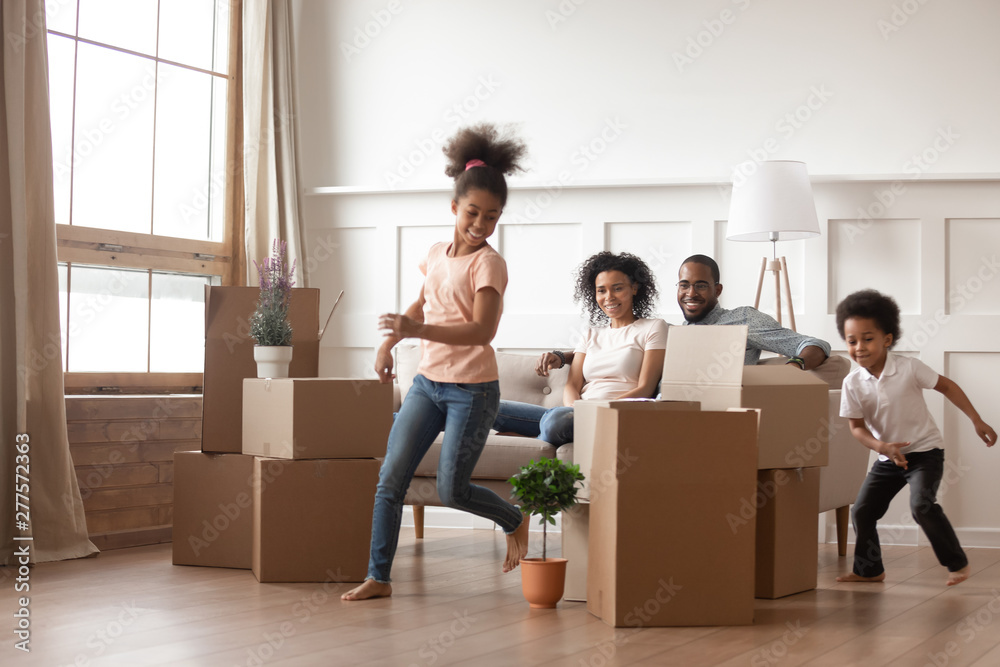Fototapety, obrazy: Active african kids running around boxes laughing on moving day