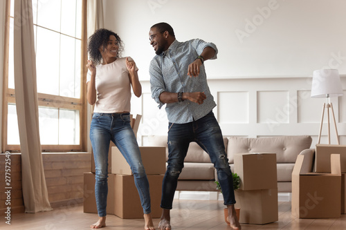 Happy african couple dancing laughing in living room with boxes - 277572549