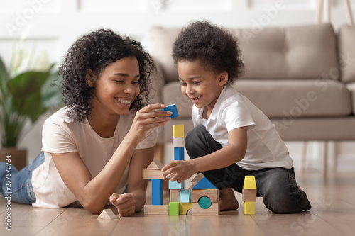 Leinwand Poster African mother with little kid son play with wooden blocks
