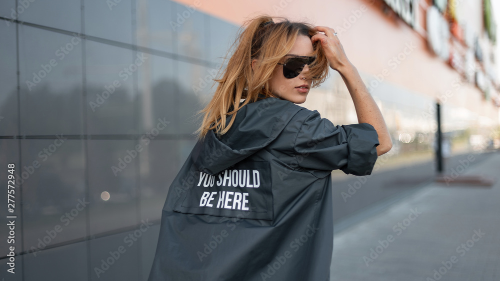 Fototapeta Urban attractive young hipster woman in stylish long jacket in fashionable sunglasses travels on a city near a modern gray mall. Trendy red-haired girl model enjoys a bright sunny day. Street style