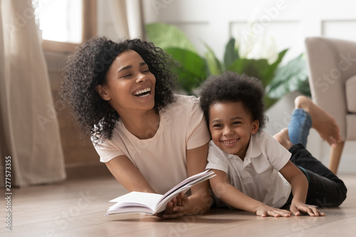 Fotografía  African mom reading book laughing with child son at home