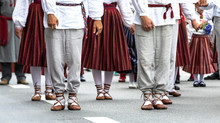 Estonian People In Traditional Clothing Walking The Streets Of Tallinn