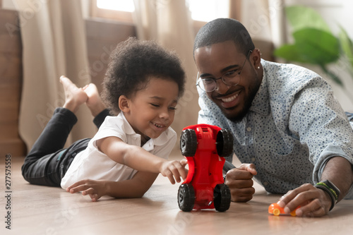 Valokuvatapetti Cute little african kid son playing toy cars with dad