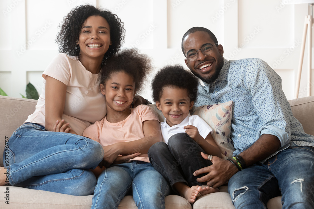 Fototapety, obrazy: Happy african family of four looking at camera at home