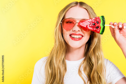 beautiful happy girl in sunglasses with lollipop in shape of watermelon Isolated On yellow