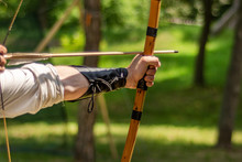 Archer Hand Holds His Bow With An Arrow And Aiming At The Target Outdoor Activity In Forest. Medieval Sport Concept. Close Up, Selective Focus