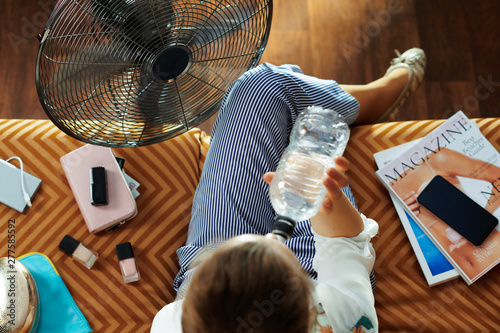 Fotobehang Hoogte schaal trendy housewife using fan and drinking water