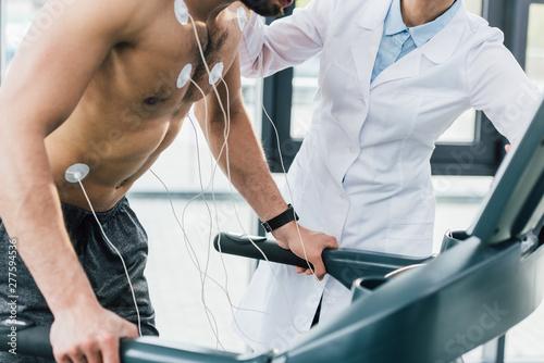 Fotomural  cropped view of doctor putting electrodes on shirtless sportsman during enduranc